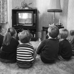 kids watching television in black and white